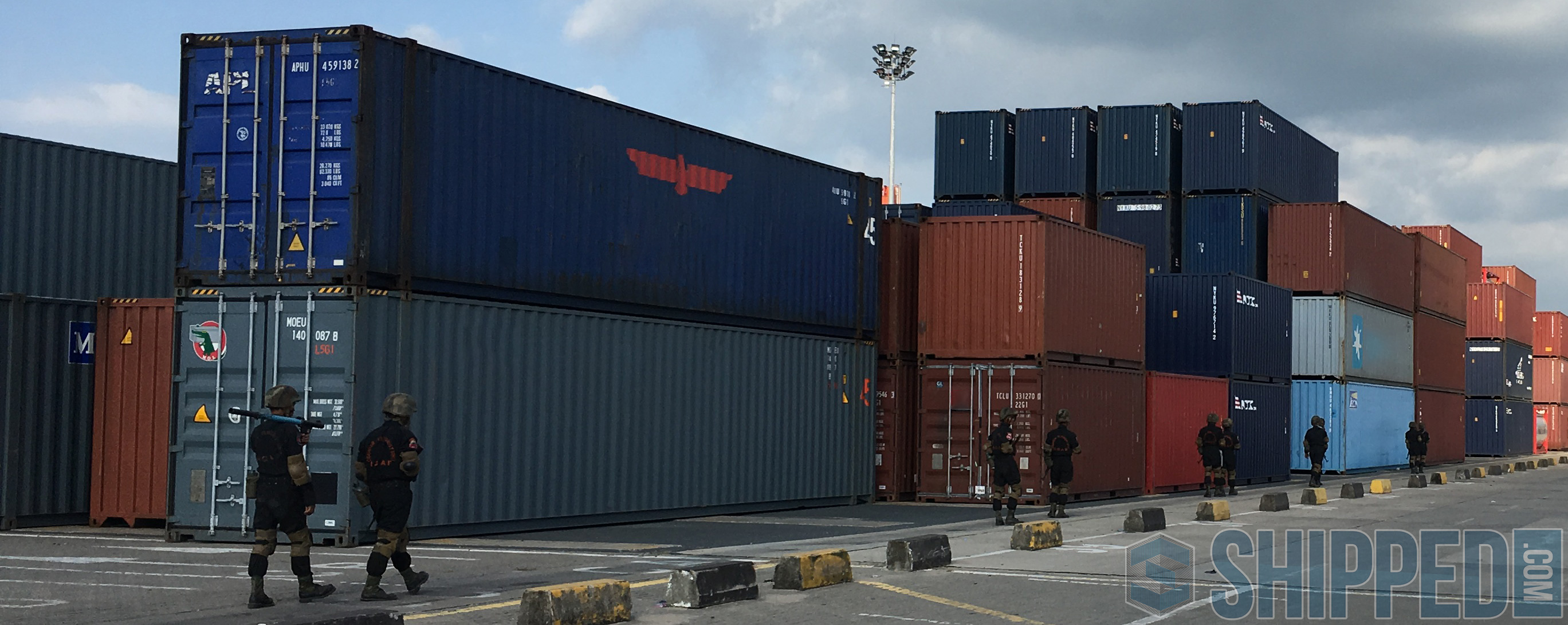 Armed guards patrol a shipping container depot