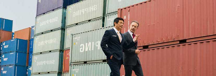 two men converse while walking through a shipping container depot