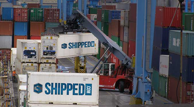 Shipping Container port with Shipped.com containers being unloaded