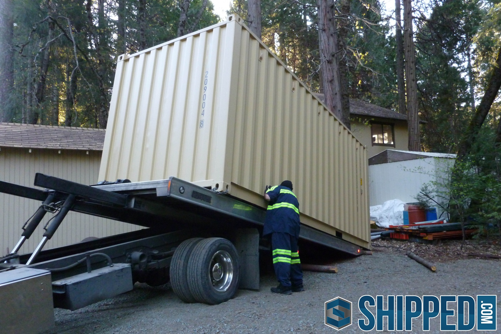 shipping container being unloaded in the backyard